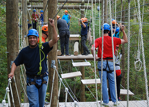 Adults doing the ropes course at Camp Weaver